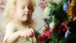 beautiful little blonde girl decorates the Christmas tree