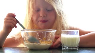 beautiful little girl eating cereal with milk