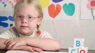 beautiful little girl in glasses sits at a school desk - dolly shot
