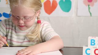 beautiful little girl in glasses with a pencil draws