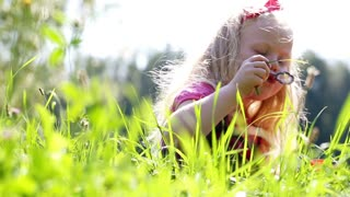 beautiful little girl inflates soap bubbles in the park - dolly shot