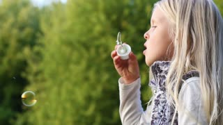 beautiful little girl inflates soap bubbles in the park