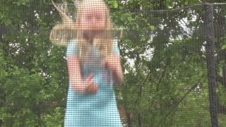 beautiful little girl jumping on a trampoline