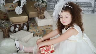 beautiful little girl opening presents around the Christmas tree