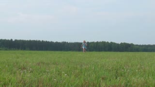 beautiful little girl runs across the meadow