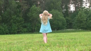 beautiful little girl spinning in a meadow