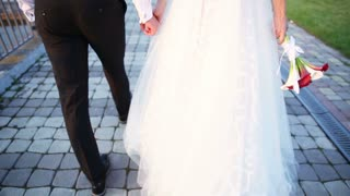 bride and groom walking down the street holding hands