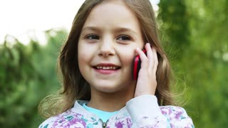 cute little girl is in the park and talking on the phone