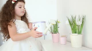 Cute little girl watering the flowers at home from a watering can