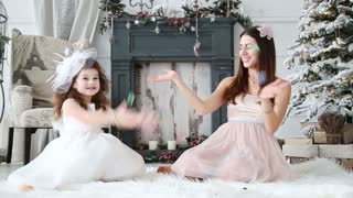 funny mom and little daughter throw confetti around them