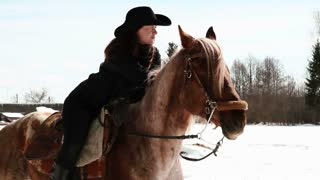 girl cowboy sitting on a horse in winter