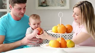happy young family with baby eats in the kitchen