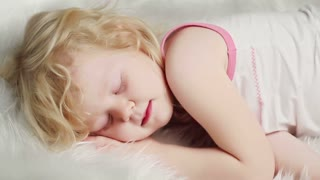 little blond girl sleeping on white bed