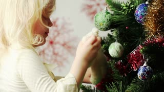 Little blonde girl decorates the Christmas tree