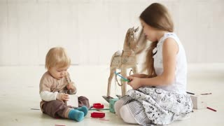 Little boy playing with a girl on the floor in a bright room