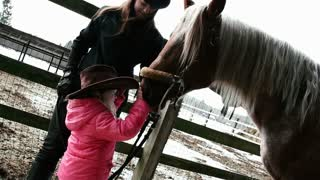 little girl in a cowboy hat petting horse