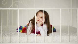 little girl lies on a big white bed in a bedroom