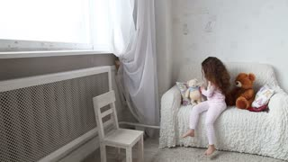 little girl playing with teddy bears on the couch and looking out the window
