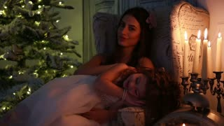 little girl sleeping in the lap of mother on Christmas night