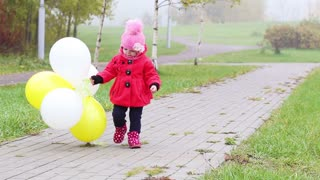 little girl walks in the autumn park with balloons