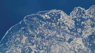 melting ice closeup on blue background. accelerated shoot