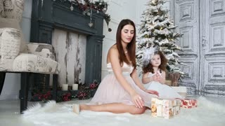 Mom and daughter opening presents around the Christmas tree