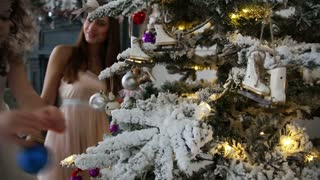 Mother and little daughter decorate a Christmas tree