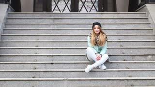 Street fashion. Cute models sitting on the stairs on a city street.
