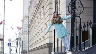 Street fashion. Happy cute girl having fun on a city street.