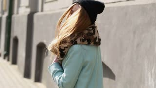Street fashion. Pretty model walking on a city street.