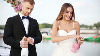 the bride and groom open champagne at a wedding