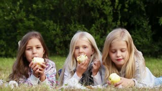 Three girls eating apples in the park