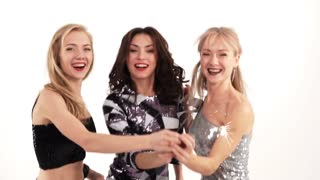 3 beautiful cheerful girls with bengal lights dancing in the studio on a white background - slow motion
