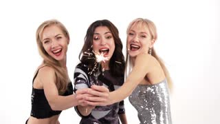3 beautiful cheerful girls with bengal lights dancing in the studio on a white background