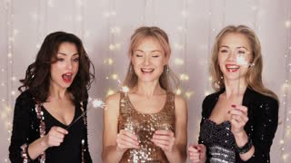 3 beautiful girls at a party dancing with Bengal lights