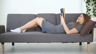 A European-looking girl reads a book at home at home on a gray sofa in the living room