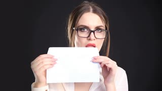 beautiful business woman sexy licking an envelope on a black background