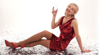 beautiful girl in red dress posing in studio with a glass of champagne on a white background - slow motion