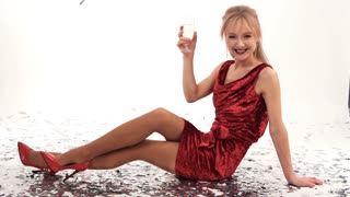 beautiful girl in red dress posing in studio with a glass of champagne on a white background