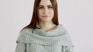 beautiful girl of european appearance in a warm sweater poses against a white wall. emotions - calmness and a smile.