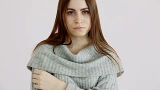 beautiful girl of european appearance in a warm sweater poses against a white wall. emotions - calmness and sadness