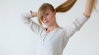 beautiful long-haired girl of European appearance with blond hair making different hairstyles over white background