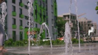 Belarus, Minsk - August 2018 - modern life in a big world - children have fun running around the city fountain