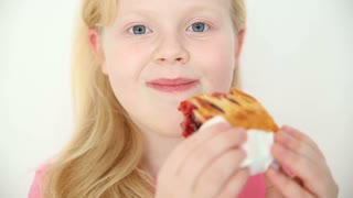 blonde girl eats cherry pie on white background close-up