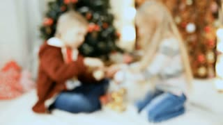 boy and girl posing near Christmas tree indoors