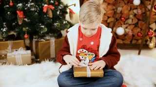 boy open gifts in the Christmas interior