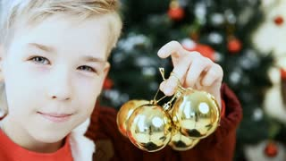 boy posing near Christmas tree indoors