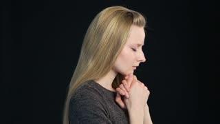 emotional portrait of a blond girl on a black background