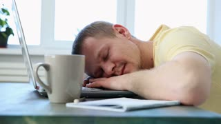 freelance programmer falls asleep from fatigue at his desk with a laptop