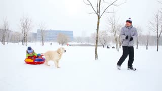 happy family with children and a dog having fun in a snow-covered park in winter